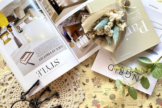 デスクトップの風景。卓上カレンダー、メモパッド、けしごむ、ノート、ペンケースからこぼれたボールペン。ガラス瓶に立てられたペンとはさみ。一輪挿しに活けられたラナンキュラスの花。
