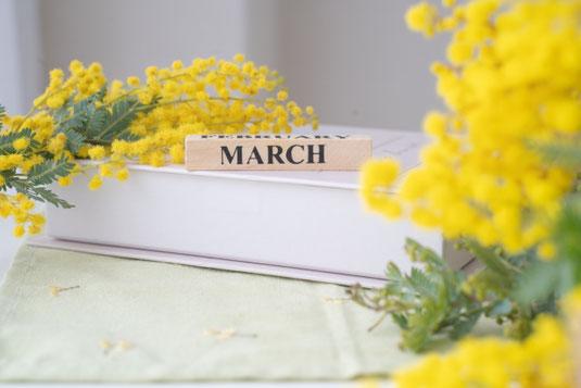 デスクに置かれたキュービックパネル式のカレンダー。白のダリアの花。