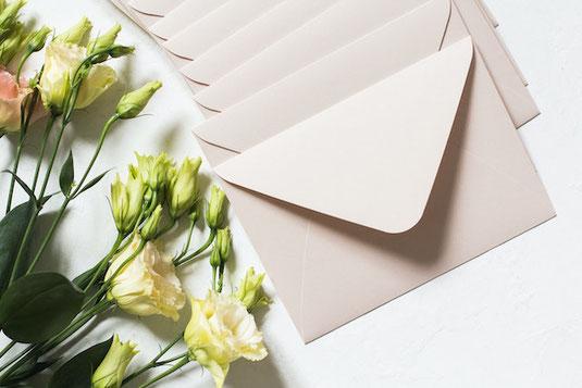 女性社員がノートパソコンのキーボードに打ち込んでいる。傍らにテイクアウトのホットコーヒー。