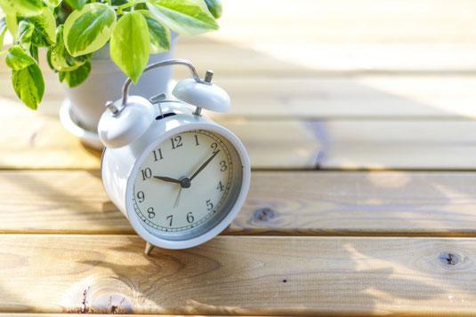 木目調のデスクに置かれた目覚まし時計。鉢植えの観葉植物。