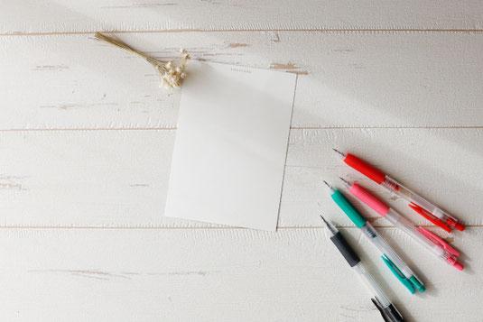 白のバラとピンクのチューリップ。モンステラの葉。パソコンのキーボード。電卓。マウス。スマートフォン。