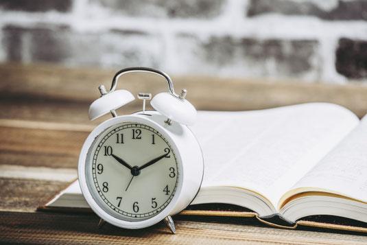 壁際のデスクに広げられた書籍。白のレトロな目覚まし時計。