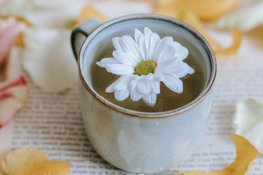 オフィスのデスクでパソコンに向かうビジネスウーマン。ブラウスにネームプレートを下げている。コーヒーを飲んでほっとひといき。
