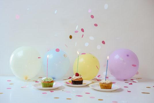 オフィスのデスク。ノートパソコンに置かれたリーディンググラスとスマホ。鉢植えの観葉植物。コーヒーの入ったマグカップ。