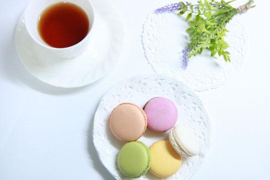 籐のトレイに載せられた2客のカップ&ソーサ。ガラスの花びんに活けられた花。