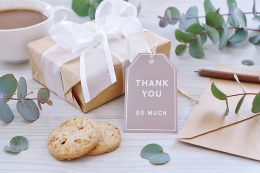 パソコンのキーボード。ピンクと白の手帳。腕時計。シャープペンシル。カラフルな付箋。コーヒーのマグカップ。バラとカスミソウのブーケ。