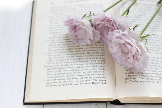 ページが開かれた書籍のうえにマーガレット、ラベンダー、バラ。