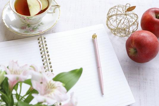 広げられたノートとピンクのボールペン。赤いリンゴが2つ。りんごのスライスを浮かべた紅茶。ガラスの瓶に活けられたユリの花。