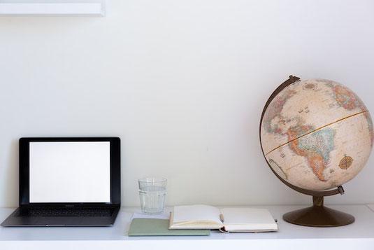 地図上の目的地に赤のピンを指す。飛行機のおもちゃ。
