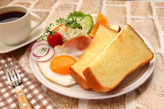 パソコンのキーボード。リングノートとボールペン、メモパッド。ピンク色の目覚まし時計。リーディンググラス。