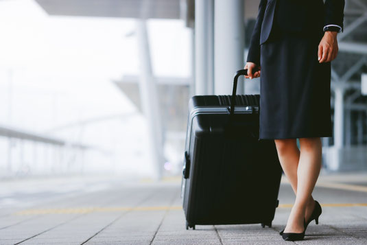 スーツケースを引くビジネスウーマン。ビジネススーツ姿。