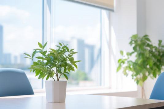 デスク前の壁に貼られたカレンダー。ピンクの花が活けられた一輪挿し。