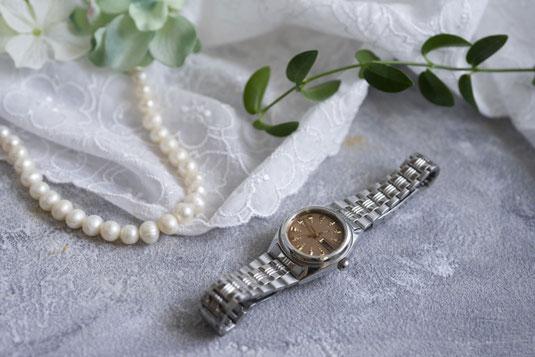 広げられた革のシステム手帳。コーヒーの入った白のマグカップ。ノートの上に置かれたカラーのボールペン。
