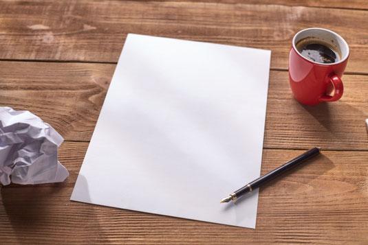 英字新聞のうえにずらりと置かれた本。べっ甲フレームの眼鏡。