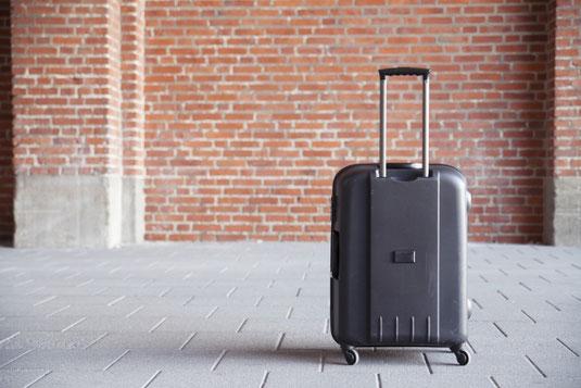 レンガの通りに置かれたグレーのスーツケース。