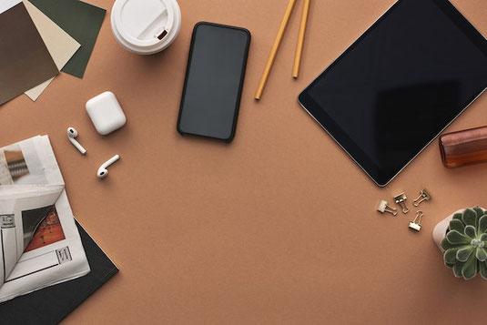 オフィスのデスク。パソコンのキーボード、レトロな置時計、手帳とボールペン。