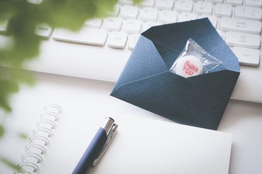 パソコンのキーボードの前に置かれた紺色の封筒。お菓子入り。広げられたリングノートとボールペン。観葉植物のグリーン。