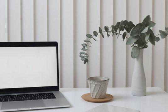 机の上に、家のミニチュア模型3体、観葉植物、電卓が並んでいる。