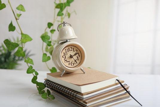 デスクに積まれたノートと書籍。そのうえに置かれた白のアンティーク調の目覚まし時計。観葉植物のグリーン。