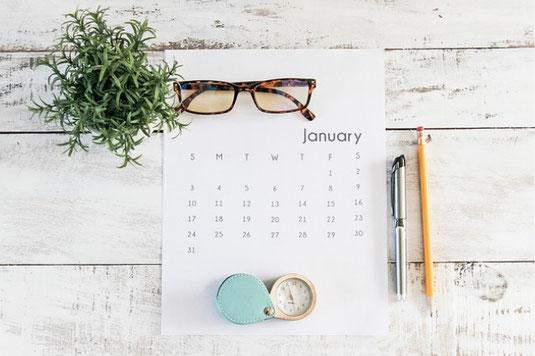 水色の椅子の上に置かれた置時計と鉢植えの観葉植物。