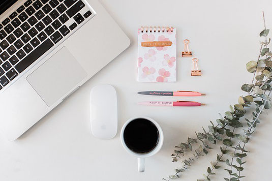 白いデスクのうえ。ノートパソコン、マウス、コーヒーの入ったマグカップ、ピンクのペン、メモ帳、クリップ、観葉植物。