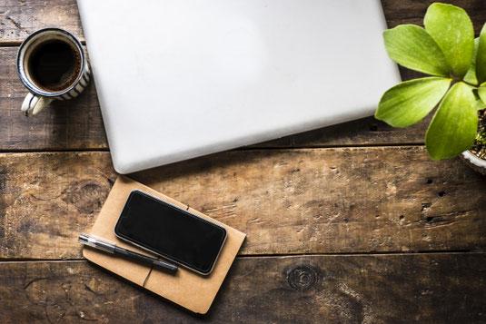 木製のテーブルに置かれたノートパソコン。手帳とスマートフォン。ボールペン。観葉植物の鉢植え。コーヒーの入ったマグカップ。