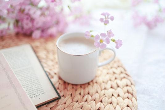 ページが開かれた分厚い洋書。そのうえに無造作に置かれたオレンジのガーベラ。