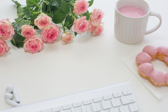 パソコンのキーボードとイヤホン。ナプキンの上に置かれたイチゴチョコのかかったドーナッツ。イチゴミルクが入ったマグ。ピンクのバラのブーケ。
