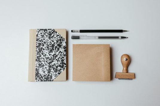 パソコンのキーボード。手帳とボールペン。お皿に盛られたチョコレートクッキー。ガラスの耐熱マグに入ったカフェラテ。