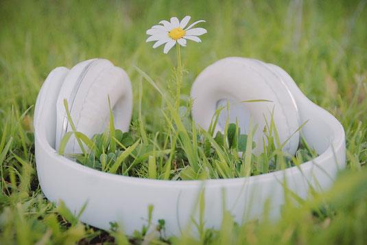 パソコンのキーボード。ピンクの手帳のうえに置かれた白の腕時計。シャープペンシルとカラフルな付箋。ミルクティーの入ったピンクのマグカップ。カーネーションとカスミソウのブーケ。