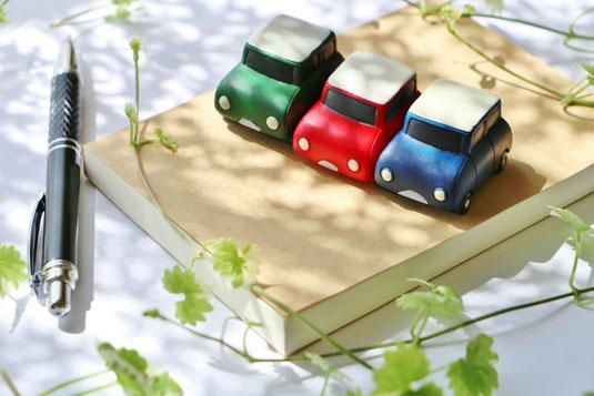 カバーが掛けられた本のうえに並べられた3台のミニカー。傍らに黒のボールペン。