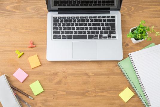 デスクに置かれたノートパソコン、リング式のノート。ペンケースからペンが飛び出している。カラフルなクリップと付箋。ミニサイズの卓上グリーン。