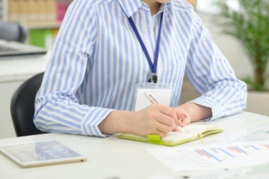 ノートのアイデアをみながら付箋にメモする女性の手。