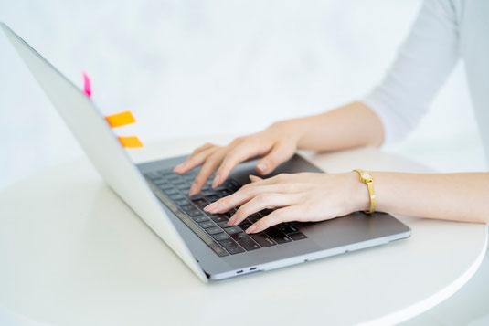 ノートパソコンに向かってタイピングする女性の指先。パソコンに付箋が貼られている。