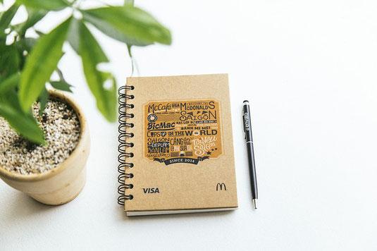 デスクの上の観葉植物、ノートとぺン。