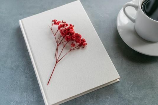 窓辺に置かれたフラワーアレンジメントのギフトボックス。ピンクのメッセージカードと封筒付き。