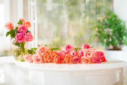 白の一輪挿しが2つ。それぞれに活けられたピンクとブルーのアジサイの花。