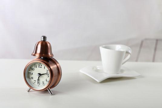 テーブルの上に置かれたレトロな置時計。白のマグカップ。