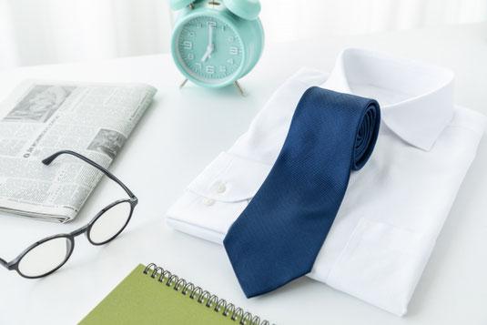 デスクに広げられたノートパソコンとタブレット。コーヒーの入った白のマグカップ。卓上サイズの観葉植物の鉢植え。