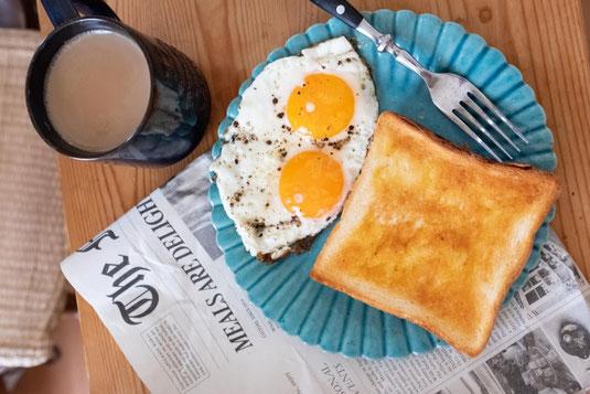 デスクに置かれたブタの貯金箱。白の電卓。メモ帳とボールペン。バラのつる。
