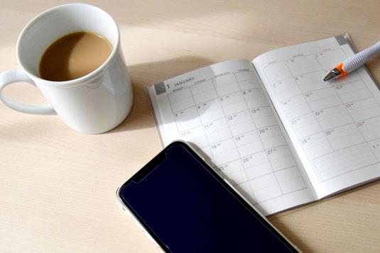 広げられたノートとピンクのボールペン。ハーブティーが入った白のカップ&ソーサ。ピンクとモスグリーンのマカロン。