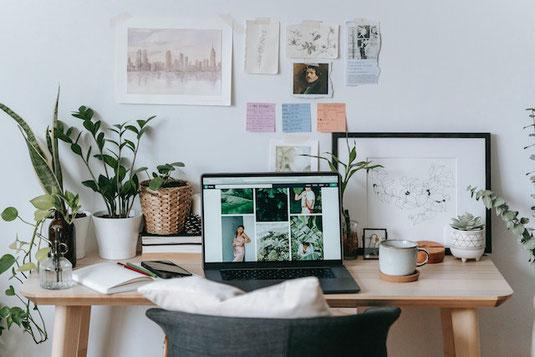 自宅の部屋。ソファセット。チューリップの花びんと果物が盛られた鉢。傍らに仕事スペース。
