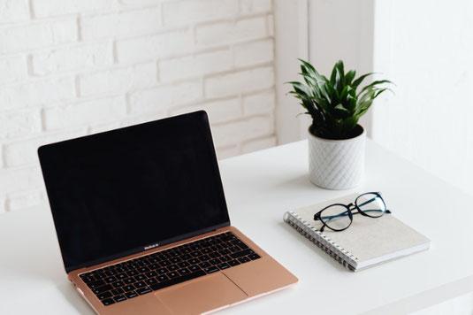 木目調のテーブルに広げられたノートパソコン、付箋、2冊のリング式ノート。卓上サイズの観葉植物。
