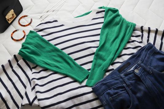 畳まれたシャツ、デニムが積まれている。その上に黒縁の眼鏡。
