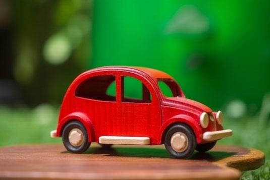 手のひらサイズのメモ帳のわきに並べられた色鉛筆。黄色、黄緑、オレンジ。おもちゃのミニカー。