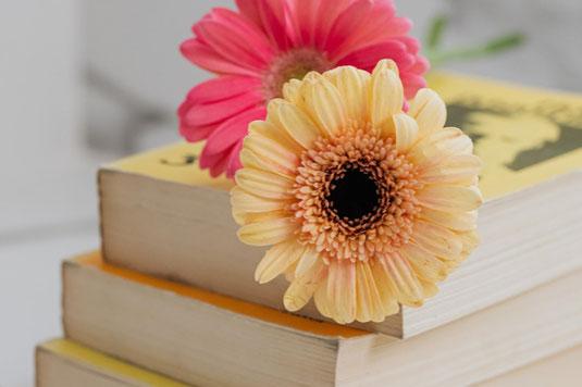 チューリップの花束、コーヒーの入ったカップ&ソーサ―、ノートがテーブルに並んでいる