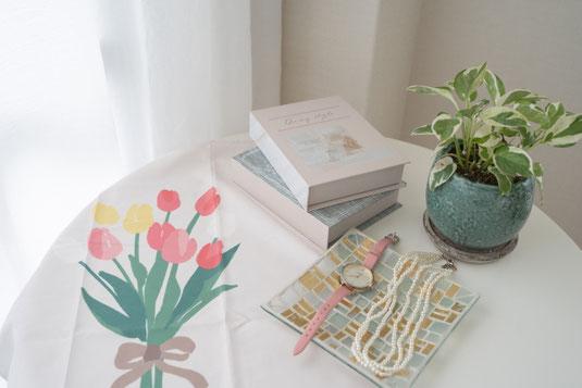 デスクに積まれた資料のファイル。メモ帳。イヤホン。2本の万年筆。コーヒーの入ったカップ&ソーサ。観葉植物の鉢植え。