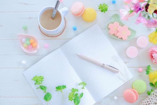 デスクに広げられたカレンダーの上に置かれた赤の目覚まし時計。