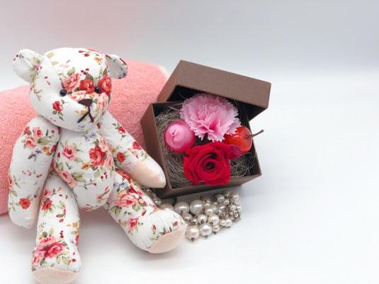 バラの生地で作られたテディベア。ふかふかのピンクのタオル、バラ、カーネーションの花。出産祝い。ギフトボックス。