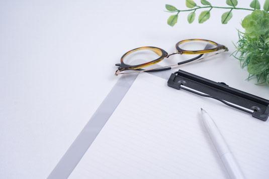 バインダーファイルとボールペン。べっ甲フレームの眼鏡。観葉植物のグリーン。